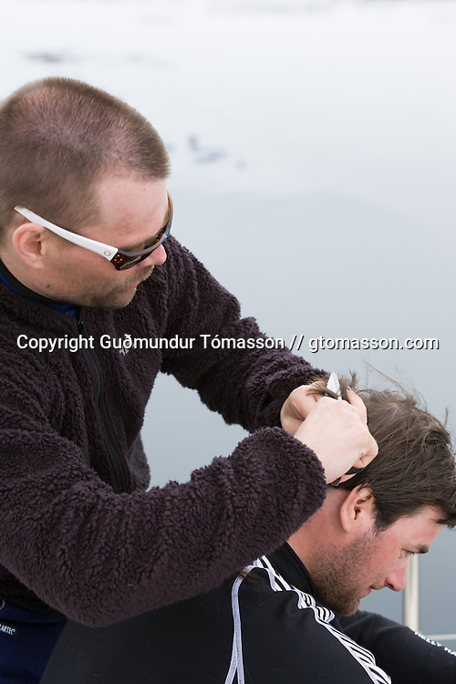 Petri Kurki getting a haircut onboard the Aurora, Vey&eth;ileysufj&ouml;r&eth;ur, Iceland.<br /> <br /> Images from an ski touring adventure to J&ouml;kulfir&eth;ir, a series of fjords in west Iceland, with Bergmenn Mountain Guides and Borea Adventures. The tour takes skiers from fjord to fjord with the sail boat Aurora as a overnight base.