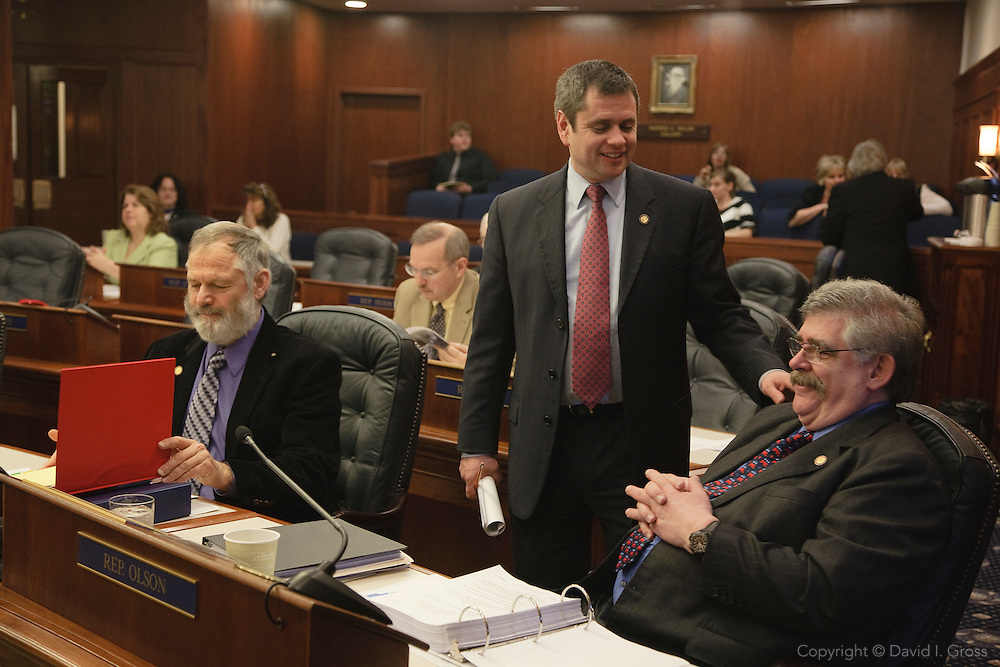 Alaska Representative Chris Tuck (D) chats with Representatives Paul Seaton (R) (left) and Kurt Olson (R) (right) on the House floor.