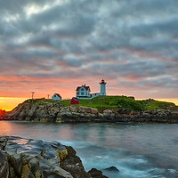 Cape Neddick Light and Boom Island Light far in the distance taken at sunrise in York, ME. Loved watching this sunrise and capturing a sun star of the rising sun while the first light created a beautiful sky across one of Maine's most scenic lighthouses, Nubble Light. Early morning is my favorite time of the day, when I can enjoy quietude and solitude.<br />