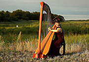 Harpist, Katie Lynch, is photographed with Quivet Creek Marsh behind her in Dennis, MA.