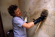 Council Cleansing Dept worker wearing rubber gloves using a brush to clean graffitti from a wall in a public toilet ......