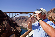 19 AUGUST 2010 --  HOOVER DAM, AZ:  Richard Farassato, from Henderson, NV, photographs Hoover Dam with the new bridge behind him. Construction work is continuing on the Hoover Dam bypass bridge. The Colorado River Bridge is the central portion of the Hoover Dam Bypass Project. Construction on the nearly 2,000 foot long bridge began in late January 2005 and the completion of the entire Hoover Dam Bypass Project is expected in late 2010.  When completed, this signature bridge will span the Black Canyon (about 1,500 feet south of the Hoover Dam), connecting the Arizona and Nevada Approach highways nearly 900-feet above the Colorado River. PHOTO BY JACK KURTZ