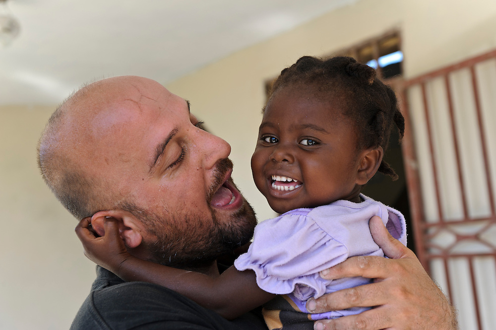 Andy Chaggar with a young girl at an orphanage supported by EDV, Port-au-Prince, Haiti. EDV is committed to affecting permanent change in disaster-affected communities worldwide. Their role is to facilitate personal connections between volunteers and the survivors of disasters.  The charity is based on a proven model developed by several landmark organisations that have paved the way for citizens to become disaster volunteers. These landmark organisations have shown that supposedly ordinary people working together with the guidance of knowledgeable leaders can make an extraordinary difference in the lives of those affected by disaster..EDV believe that to provide meaningful relief and reconstruction assistance to disaster affected communities they have to do more than reconstruct buildings. They need to understand and address the factors that made a community vulnerable to the disaster in the first place. The charity's work is organised with these factors in mind so that they can affect change that far outlives their presence..EDV believes that survivor motivation is essential to the recovery of any disaster-affected community. Their operations will always be predicated on the idea that survivors may be traumatised, but they are not helpless. With this in mind, EDV encourages host communities to direct their own recovery. EDV believe that this empowerment is essential in helping survivors feel a renewed sense of control over their lives which will, in turn, help overcome the feelings of hopelessness that can follow a disaster and inhibit long term recovery. EDV also believe that social cohesion is of primary importance in any disaster-affected area. No amount of bricks or mortar will bring about sustainable improvement if communities fail to come together or are disrupted by relief efforts. Therefore, their operations will always aim to foster communication and cooperation within and between the communities they serve.