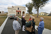 "Greensburg, Kansas, USA..Catherine Hart (center, red sweater) program director of Greensburg GreenTown,  leads a tour of Greensburg, in front of The Greensburg Silo Home. ..With precast concrete walls and a cylindrical form, this house will stand up to very strong winds. It also has a LEED rating of level 47. The Greensburg Silo Home is a part of The Chain of Eco-Homes--a series of twelve green houses that will serve as ""living laboratories"" featuring all types of building techniques, energy efficiency features, and green living products. Each will be available both as an informational center and as eco-lodging where people can experience green living first-hand...Greensburg GreenTown is a grassroots community-based organization which has worked side-by-side with city and county officials, business owners and local residents to incorporate sustainable principles into their rebuilding process. GreenTown serves as an educational resource for the community, a conduit through which donations can be distributed, and a representative to those outside the community who are interested in the Green Initiative...""Greensburg: Better, Stronger, Greener!"".On May 4, 2007, an EF5 tornado cut a 1.7-mile path of destruction through Greensburg, Kansas. Winds reaching speeds of 205 miles per hour uprooted trees, demolished homes and leveled the town. Eleven people died and 95% of the buildings were destroyed beyond repair. Residents have since worked furiously to rebuild it in a way that is both economically and environmentally sustainable and to meet the highest environmental standards. Greensburg, whose population has dropped from about 1400 to 800 following the storm and is now growing again, is currently the greenest town in America and the first in the United States to pass a resolution to certify that all city-owned buildings earn LEED Platinum accreditation, the highest level of the LEED rating system...Foto © Stefan Falke"