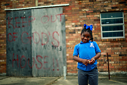 27 August 2014. Lower 9th Ward, New Orleans, Louisiana.<br /> Hurricane Katrina 9 years later. Calsey Harris (6 yrs) stands outside a derelict church just purchased by Pastor Darrell Turner of the Disciples of Christ Christian Fellowship. Bringing hope to the neighborhood still struggling to recover from hurricane Katrina, Pastor Turner hopes to have the renovations completed within a year, ready for the 10th anniversary of the storm. <br /> Photo; Charlie Varley/varleypix.com