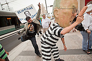 """19 JUNE 2009 -- PHOENIX, AZ: Adolfo Maldonado (CQ) from Phoenix, pretends to kick Sheriff Arpaio out of office during a demonstration in front of Wells Fargo building Friday. The Sheriff's Department is headquartered in the Wells Fargo Bank building. Rev. Al Sharpton was in Phoenix Friday to protest the high profile """"crime suppression"""" sweeps conducted by the Sheriff's Department. Critics contend the sweeps use racial profiling to target Hispanics. PHOTO BY JACK KURTZ"""