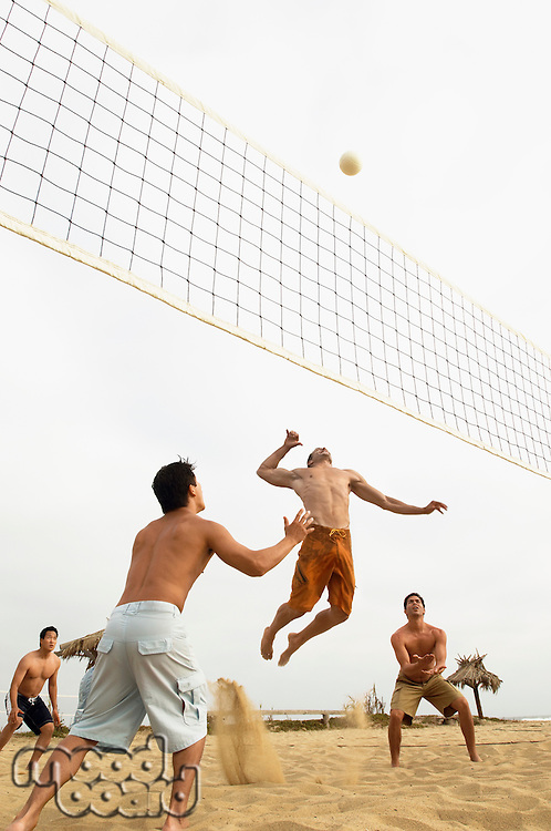 Man in Mid-air Going for Volleyball on beach
