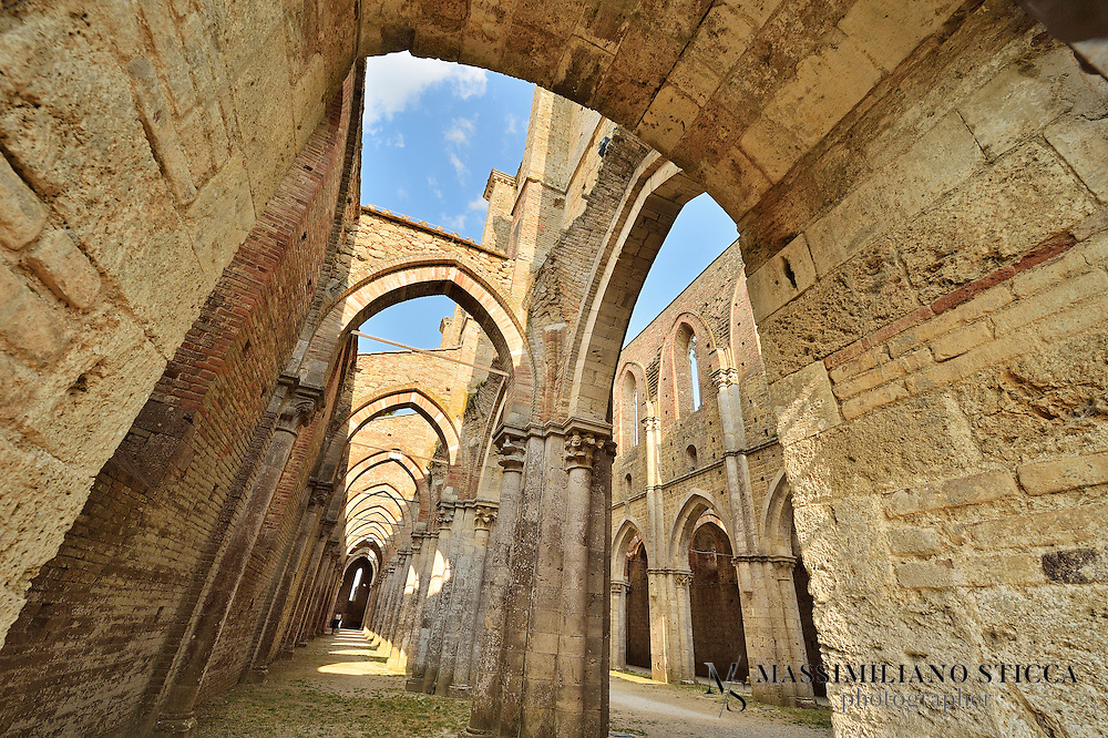 The Cistercian Abbey of San Galgano is an icon unto itself, the foremost symbol of this land.<br /> It is historically and architecturally one of the most important religious monuments in the Sienese countryside and, together with the nearby chapel at Monte Siepi, is an important expression of the gothic Cistercian style in Italy represented by the Fossanova abbey in Lazio.<br /> Architecturally, its severe, rigorously formal design was intended to exemplify the moral rigour upheld by St. Bernard. Not coincidentally, the abbey was built in an area already sanctified by the presence of the chapel at Monte Siepi, built at the end of the twelfth century to consecrate the home of the young hermit Galgano Guidotti, who died in 1181 and was canonized in 1185.<br /> The abbey was consecrated seventy years after the first stone was laid. This marked the onset of frenetic religious activity and of activity in general in an area where the valley is wide-open and sunny. First the marshy fields were drained, and then the river's flow was harnessed to produce hydraulic energy.<br /> It seems that the original design of the abbey foresaw mills for flour-making and wool processing. But in the end the abbey enjoyed only a brief life. Decline was brought on first by famine in 1329 and then by Bubonic plague in 1348, sealing the fate of this monastic settlement. In the sixteenth century the structure itself began to succumb, especially once the lead roofing was sold.