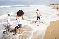 Three children walking on beach