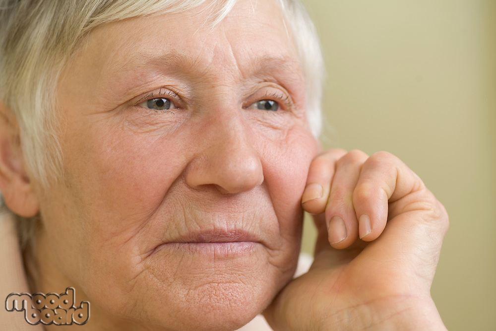 Elderly woman with short grey hair  leaning on hand
