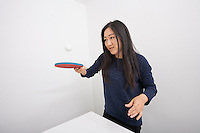 Female table tennis player bouncing ball on paddle