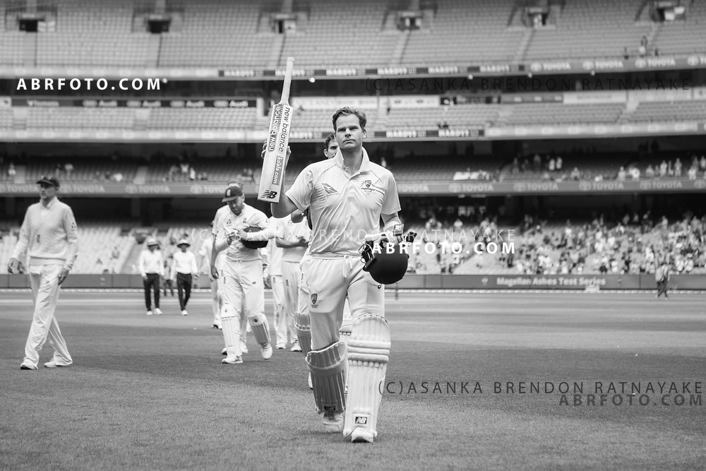 Steve Smith walks off the field with his bat raised after scoring 102 not out during day 5 of the 2017 boxing day test.