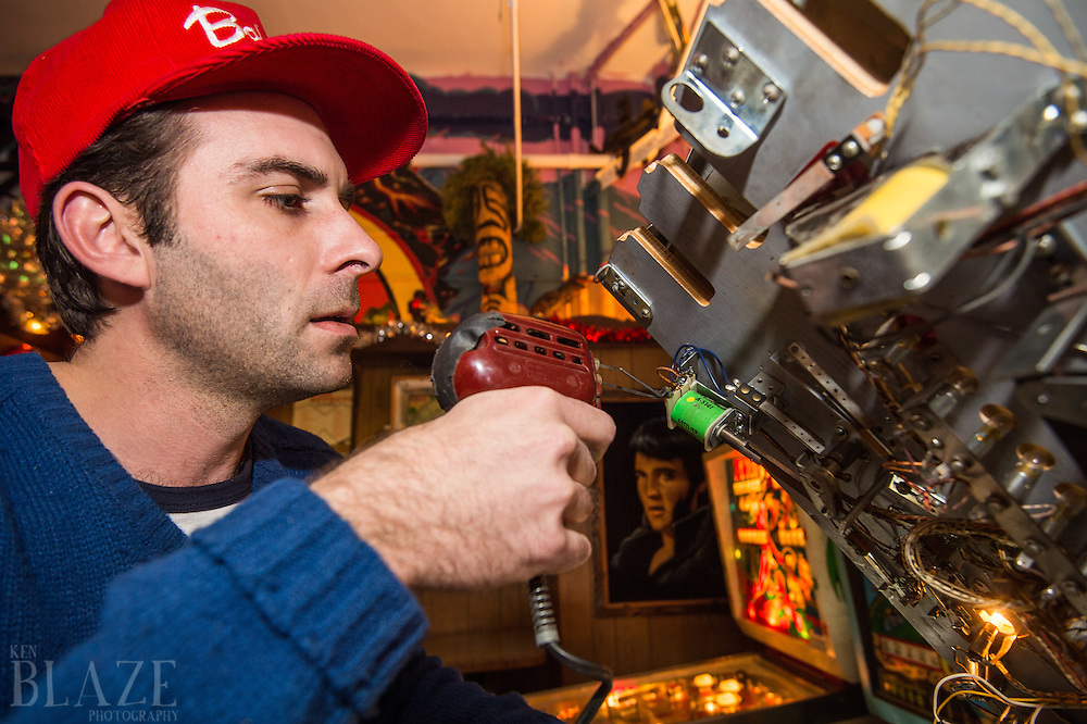 Nate Murray, part owner, works on the coin mechanism of a pinball machine at the Super Electric Pinball Parlor in the Ohio City neighborhood of Cleveland.