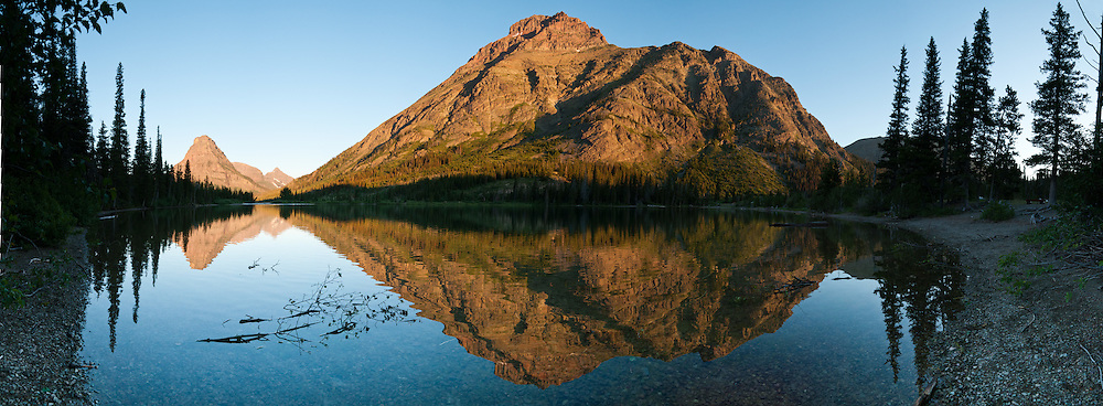 """Rising Wolf Mountain (9513 feet/2899 meters) and Sinopah Mountain (left) reflect in Pray Lake, in Glacier National Park, Montana, USA. Since 1932, Canada and USA have shared Waterton-Glacier International Peace Park, which UNESCO declared a World Heritage Site (1995) containing two Biosphere Reserves (1976). Rocks in the park are primarily sedimentary layers deposited in shallow seas over 1.6 billion to 800 million years ago. During the tectonic formation of the Rocky Mountains 170 million years ago, the Lewis Overthrust displaced these old rocks over newer Cretaceous age rocks. Glaciers carved spectacular U-shaped valleys and pyramidal peaks as recently as the Last Glacial Maximum (the last """"Ice Age"""" 25,000 to 13,000 years ago). Of the 150 glaciers existing in the mid 1800s, only 25 active glaciers remain in the park as of 2010, and all may disappear by 2020, say climate scientists. (Panorama stitched from 11 overlapping images.)"""