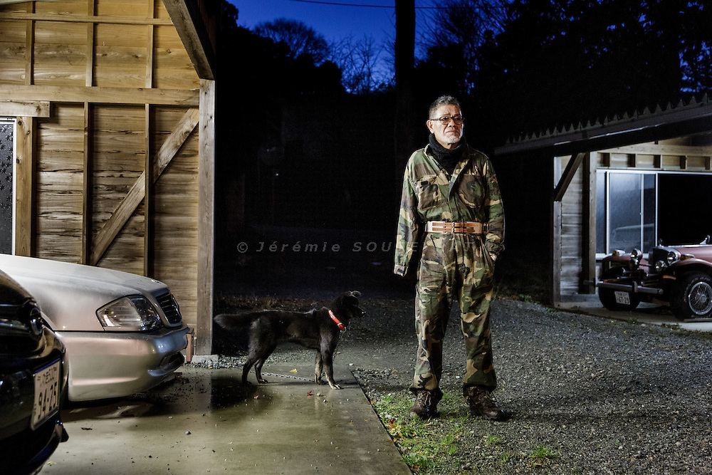 Onahma, Iwaki city, Fukushima prefecture, December 11 2014 - Hisano YANAI posing outside his former house.<br /> Hisao YANAI is a former yakuza boss of Hirono, 25km south of the nuclear power plant. He lost his right arm when he was 15 and spent 28 years in jail for various crimes during his life. He is now taking refuge in Onahama, 60 km from the plant, as it is still not allowed to live in his former house.<br /> Mr Yanai owns two boats and 6 cars and visit his former house everyday.