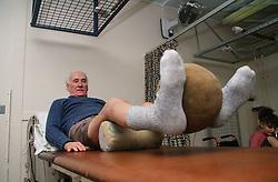 Elderly male patient lifting medicine ball between feet in order to strengthen leg muscles,