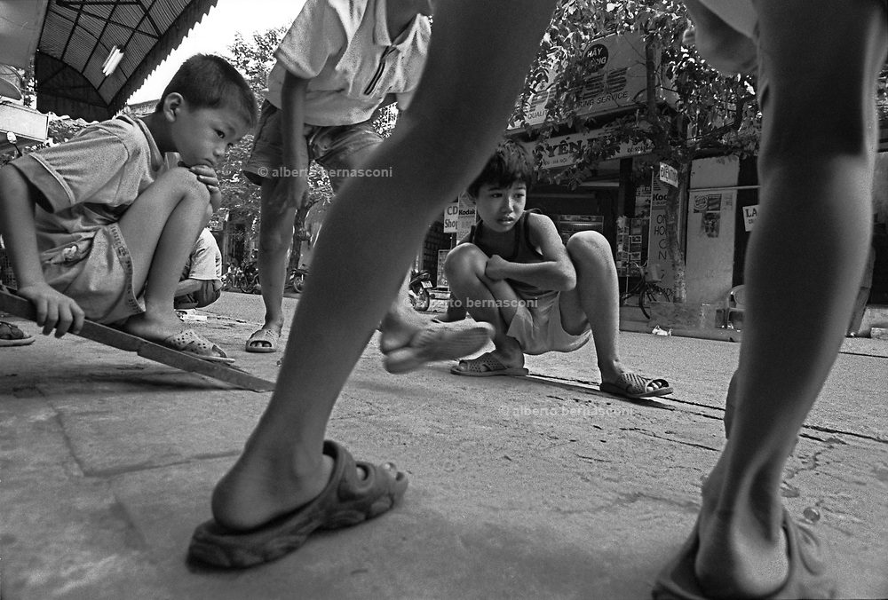 Vietnam, Hanoi: children playing with little balls on the street.