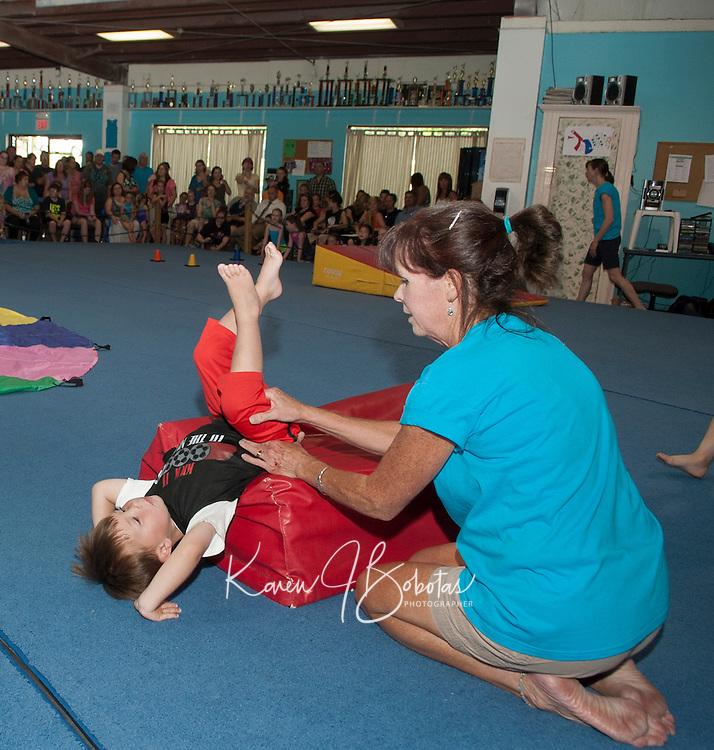 Kathy Kendrick of Lakes Region Gymnastics spots Justin Correia during his tumbling routine Friday evening.  (Karen Bobotas/for the Laconia Daily Sun)