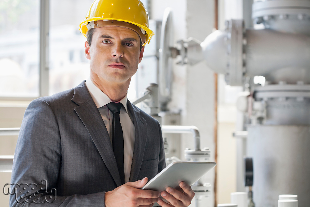 Portrait of young male architect holding tablet computer in industry