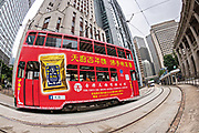 Fisheye view of a double decker tram traveling past the Old Bank of China building in the central district of Hong Kong.