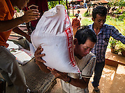 01 JUNE 2016 - SIEM REAP, CAMBODIA:  Emergency rations of rice being delivered to a village northeast of Siem Reap. Farmers in the village have not been able to buy rice because they don't have enough money. Many of the farmers in this part of Cambodia saw their income drop when their crop yields were reduced by the two year drought in Southeast Asia. There are growing concerns that spot food shortages, especially of fish, the Cambodians main source of protein, could become worse if the coming rainy season doesn't bring relief from the drought that has gripped Cambodia for the last two years.     PHOTO BY JACK KURTZ