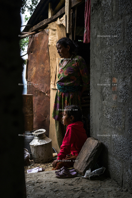 Monika (7, in red) and her grandmother Bhagawati Baniya (56) looks out of their temporary home in Chautara, Sindhupalchowk, Nepal on 29 June 2015. The three girls lost their mother during the April 25th earthquake that completely levelled their house. Aastha was buried under the rubble together with her mother but Aastha survived. As their father Ratna Baniya (28) cannot care for the children on his own, SOS Childrens Villages has since been supporting the grandmother with financial and social support so that she can manage to raise the children comfortably and ensure that they will all be schooled. Photo by Suzanne Lee for SOS Children's Villages
