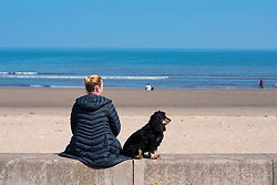 Portobello, Scotland, UK. 25 April 2020. Views of people outdoors on Saturday afternoon on the beach and promenade at Portobello, Edinburgh. Good weather has brought more people outdoors walking and cycling. Police are patrolling in vehicles but not stopping because most people seem to be observing social distancing. Woman with dog sitting on seawall.  Iain Masterton/Alamy Live News