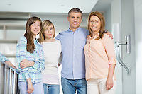 Portrait of happy parents with daughters standing together at home