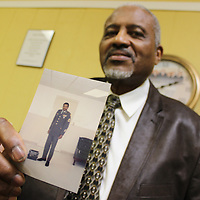 RAY VAN DUSEN/BUY AT PHOTOS.MONROECOUNTYJOURNAL.COM<br /> Cecil Belle holds a photo of himself from his National Guard years. As a non-commissioned race relations officer, he helped secure equal opportunities for African-Americans enlisting in the National Guard in the 1970s.