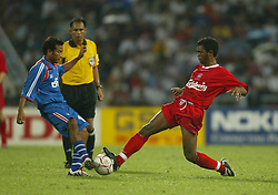 BANGKOK, THAILAND - Thailand. Thursday, July 24, 2003: Liverpool's Florent Simama-Pongolle and Thailand's Panupong Wongsa nduring a preseason friendly match at the Rajamangala National Stadium. (Pic by David Rawcliffe/Propaganda)