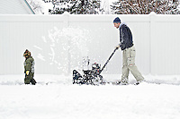 Gabe Deuling, 2, clears a path for his dad Nick Deuling who snowplows the sidewalk by their Coeur d'Alene home Wednesday following the overnight storm that dropped a fresh blanket of snow.