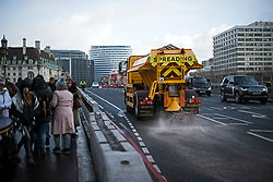 © Licensed to London News Pictures. 26/02/2018. London, UK. A glitter is seen spreading grit on Westminster Bridge in central London, as a cold front sweeps in from the east. Up to 20cm of snow are expected in parts of the UK, with temperatures feeling as low as -15C in some places. Photo credit: Ben Cawthra/LNP