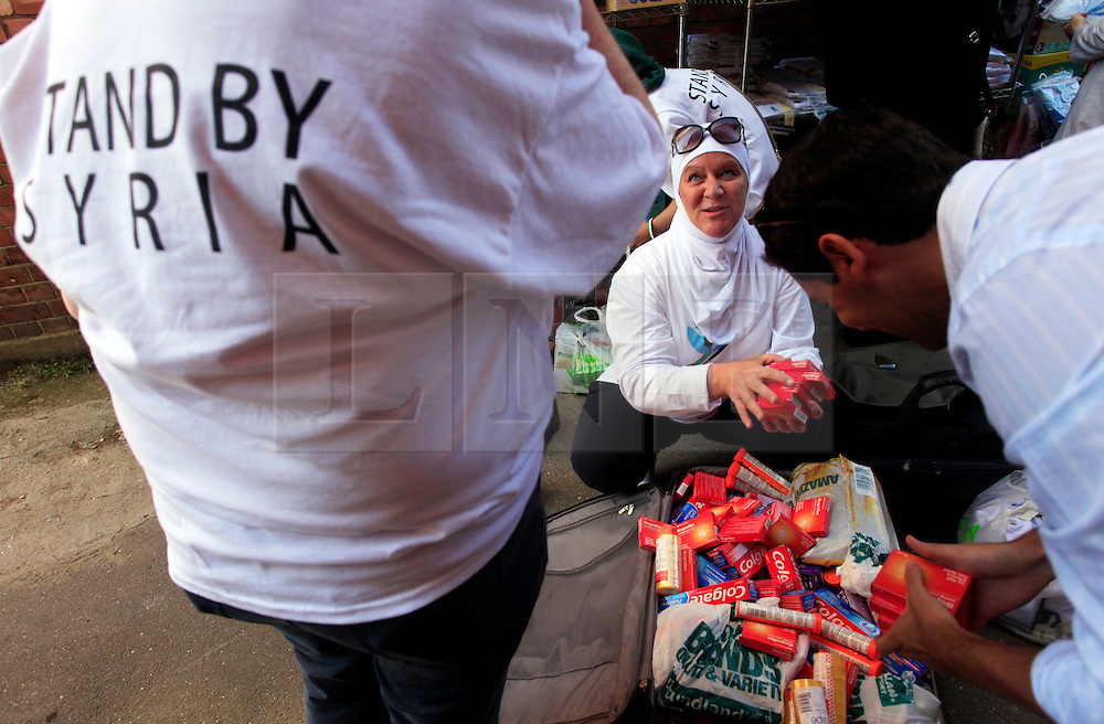 © Licensed to London News Pictures 10/04/2013<br /> Iman Mujahed, centre, one of the trustees of Hand In Hand for Syria (HIHS) receives donations from a member of the public during their national fundraising day, where supplies will then be shipped to Syria.