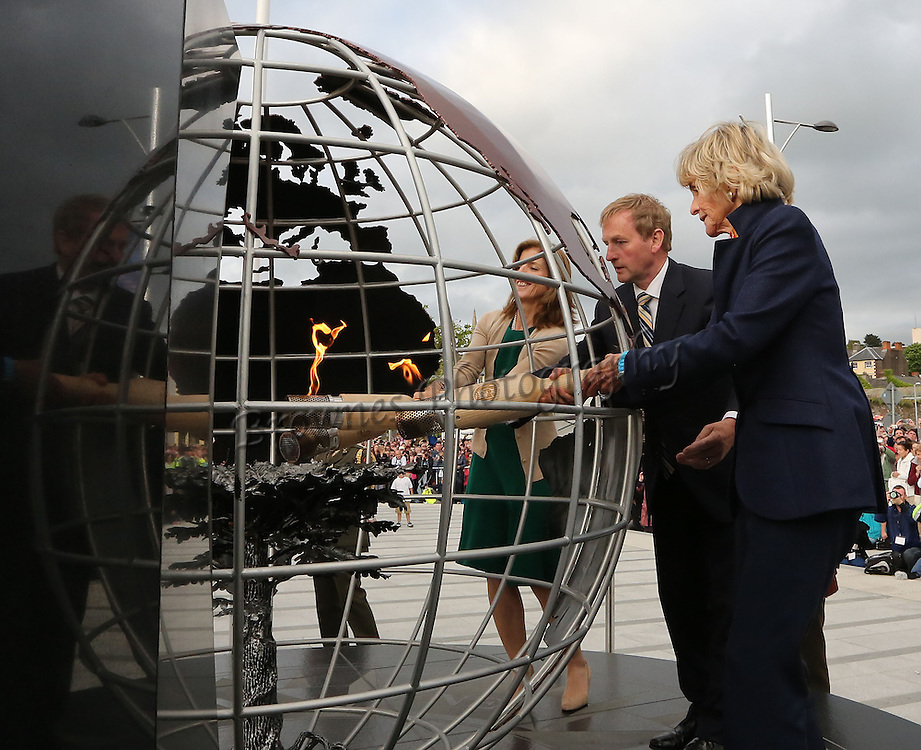 """22/06/2013. Free To Use Image. Pictured in New Ross, Co. Wexford at the JFK50. Pictured at the lighting of the emigrant flame by Former Ambassador Jean Kennedy Smith, An Taoiseach Enda Kenny and Kathleen Kennedy Townsend. Picture: Mary Browne<br /> <br /> Thousands descend on New Ross to Honour Memory of JFK<br /> <br /> The town of New Ross with a population of 7,000 saw a huge influx of visitors descend on the Quayside on Saturday afternoon to join in the commemorations and celebrations honouring their most famous Wexford sons – President John F. Kennedy.<br /> <br /> The town's streets were abuzz and coloured with red, white and blue as a US Style Parade took to the streets at 3pm lead by a national colour party and pipe band from the Irish Defence Forces.<br /> <br /> The ceremonial events opened with a moving visual of images and video of the visit of the President to the same spot on the New Ross Quayside fifty years ago.<br /> <br /> Anne Doyle and George Hook took to the stage to welcome the audience, saying """"Welcome to the quayside in New Ross – the very spot where fifty years ago this week the President of the United States of America, son of Wexford and Dunganstown, and descendant of the great Irish Diaspora of the mid 19th century, celebrated his Irish heritage and commemorated the sacrifice and the heartbreak of his great grandfather who had sailed from this quay one hundred and fifteen years before.""""<br /> <br /> Cathaoirleach of New Ross Town Council, Cllr Paul Crowdle officially welcomed the visitors """"We are all here to remember and mark the momentous occasion for New Ross, back in June 1963, a date before many gathered here today were born. There is a great affinity for the Kennedy family to Ireland and the New Ross area in particular. Jean Kennedy Smith, the late Robert and Ted Kennedy have  been hugely supportive of efforts in New Ross as well as other members of the Kennedy family who have visited the area over the years. We hope to see this cont"""