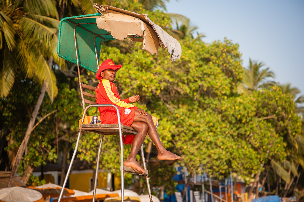 Beach guard sitting on top of chair in Goa (India)