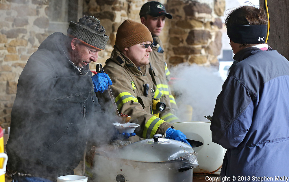 Amana firefighter Rick Kleinmeyer serves a bowl of chili to a customer during Winterfest at the Amana Colonies in Amana on Saturday, January 26, 2013.
