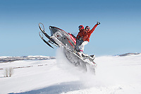 Couple jumping snowmobile in snow mid air