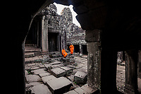 Two monks in bright saffron robes relax in the crumbling courtyard of The Bayon temple, within the Angkor Wat complex, outside of Siem Reap, Cambodia.