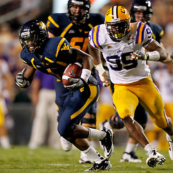 Sep 25, 2010; Baton Rouge, LA, USA; West Virginia Mountaineers wide receiver Tavon Austin (1) runs away from LSU Tigers defensive tackle Lazarius Levingston (95) during the second half at Tiger Stadium. LSU defeated West Virginia 20-14.  Mandatory Credit: Derick E. Hingle