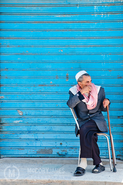 A man sits in a chair wearing a scarf and chechia in Tabersouk, Tunisia