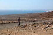 Lone man walking in barren landscape Jandia peninsula, Fuerteventura, Canary Islands, Spain