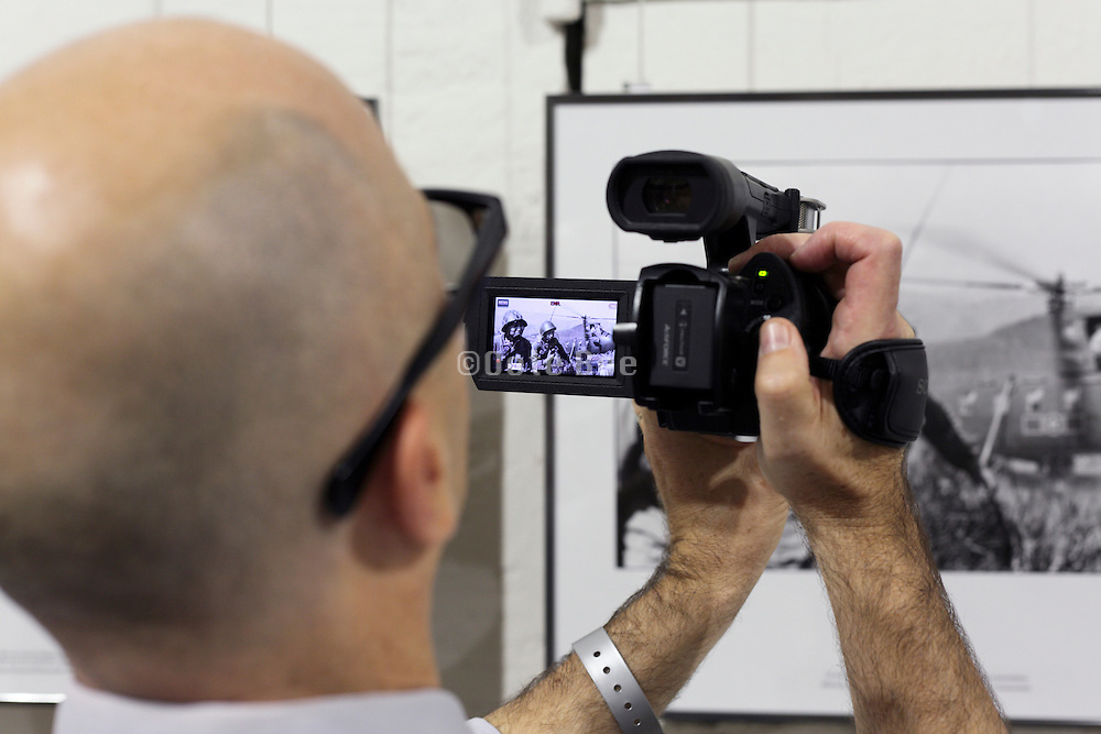 videographer filming a image from the Vietnam war during Visa Pour L'Image Perpignan 2014