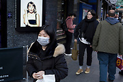On the day that the UK Government's Chief Scientific Advisor, Sir Patrick Vallance said that the Coronavirus Covid-19 outbreak was now spreading person to person in the UK, a member of the Chinese community wears a surgical mask outside the London Palladium near Chinatown in the West End, on 6th March 2020, in London, England.