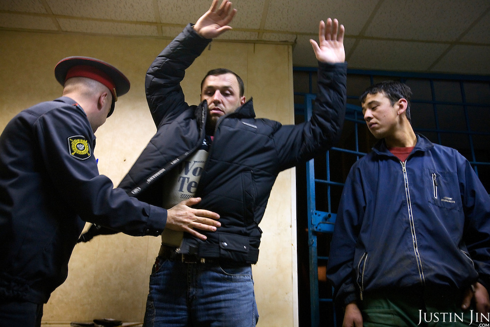 A policeman body-searches a Georgian worker before locking him in a prison cell after he and others were arrested for working without a permit in Moscow. Russia is cracking down on foreign nationals working in its markets and construction sites.