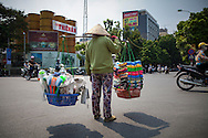Vendor stands in a street holding a yoke with full baskets in Hanoi, Vietnam, Southeast Asia