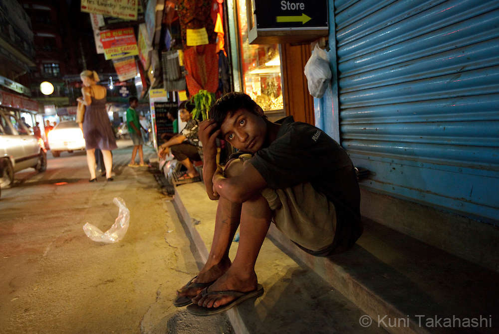 Krishna sits on the sidewalk as he gets intoxicated by sniffing glue at commercial area in Kathmandu, Nepal on Aug 17, 2012..There are estimated around 5,000 street children working and living on the streets of Nepal and the number continues to grow with roughly 300 to 500 children leaving home every year. Some do so because of abusive, alcoholic parents, maltreatment at home, and the temptation to earn more money. They often end up taking drugs, abusing alcohol, and even suffering sexual abuse by locals and foreign tourists..(Photo by Kuni Takahashi)