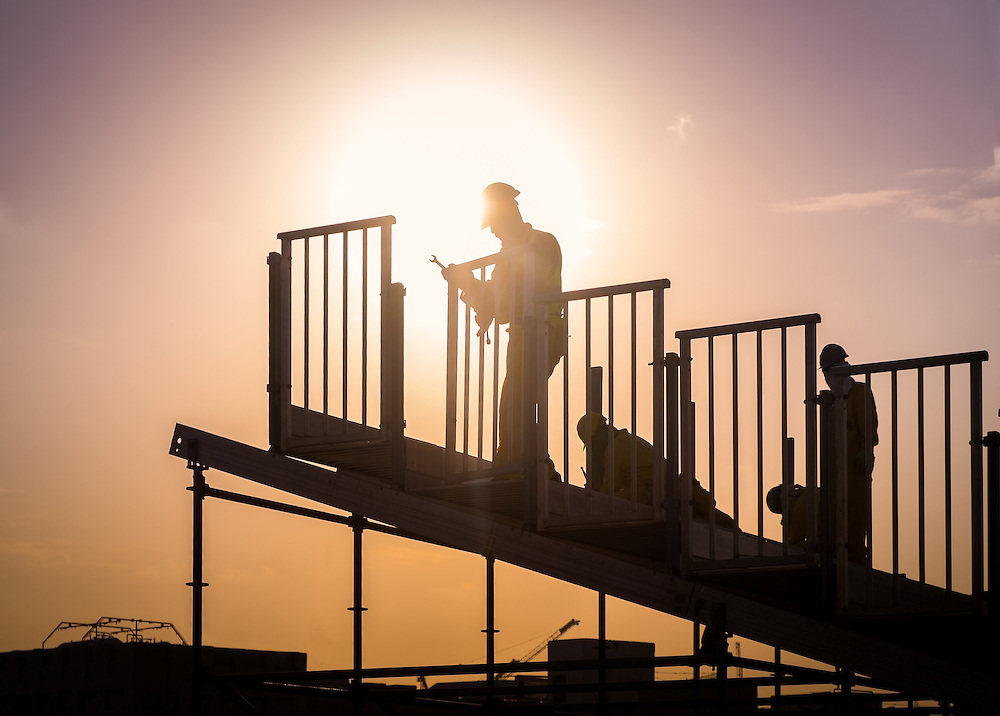 DOHA, QATAR - CIRCA DECEMBER 2013: Construction workers preparing a grandstand before a national celebration in Doha.