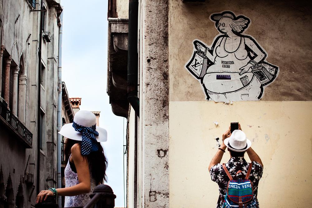Turismo e shopping. Grosso adesivo nel sestiere San Marco, sulla via dello shopping di lusso.