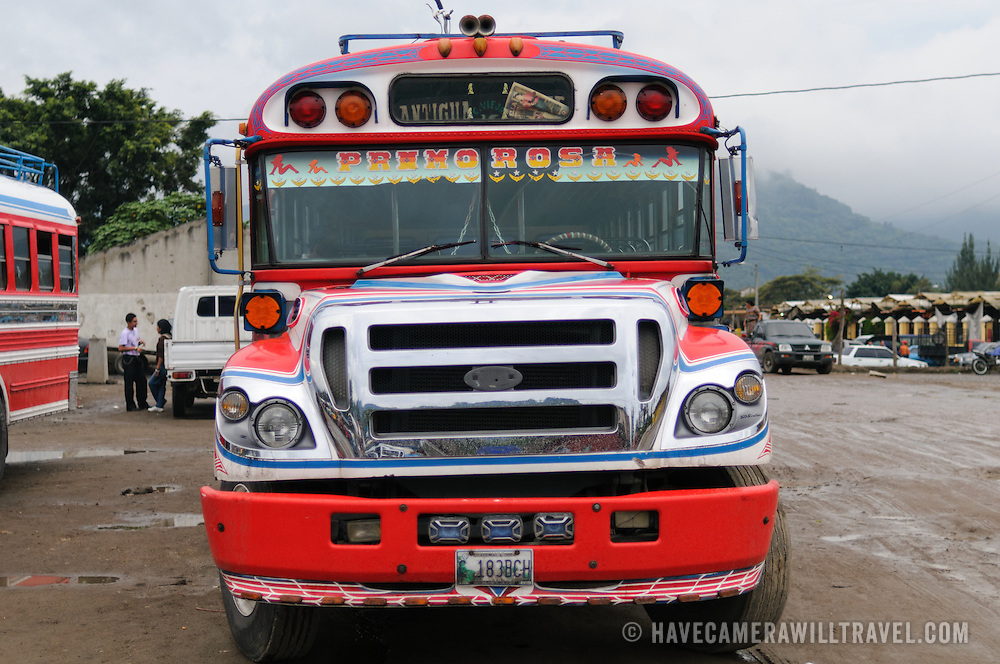 Front of a chicken bus behind the Mercado Municipal (town market) in Antigua, Guatemala. From this extensive central bus interchange the routes radiate out across Guatemala. Often brightly painted, the chicken buses are retrofitted American school buses and provide a cheap mode of transport throughout the country.
