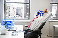 Tired businessman stretching in wrestling mask at office desk